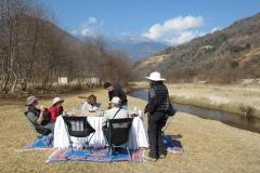 Rockjumper's 2020 Bhutan birding tour group enjoying a tea break around a popup table next to a stream