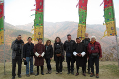 Rockjumper's 2020 Bhutan birding tour group take a group photo with mountains in the background