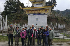 One of Rockjumper's Bhutan birding tour groups takes a group photo with a religious monument in the background