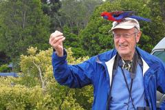 John Plummer in Lamington National Park with a friendly Crimson Rosella on his head