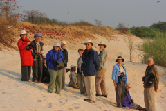 One of Rockjumper's Namibia birding tour groups take a group photo with a Southern Carmine Bee-eater colony